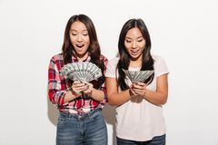 Two asian pretty shocked cute ladies holding money. Photo of two asian pretty shocked cute ladies sisters standing isolated over white background. Looking aside Stock Photos