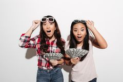 Two asian pretty shocked cute ladies holding money. royalty free stock image
