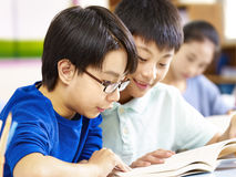 Two asian pupils studying together in classroom. Close-up of two asian elementary school pupil studying together in classroom Stock Images