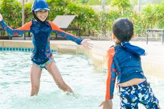 Two siblings in playing together in Water Aqua park pool royalty free stock photo