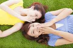 Two asian sisters whispering gossip on the grass. Land stock images
