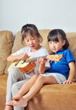Two asian small girls playing ukulele and singing together Stock Image