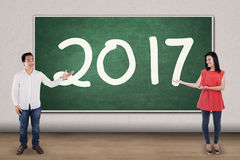 Two Asian teachers showing numbers 2017. Image of two Asian teachers is showing numbers 2017 on the chalkboard while standing in the classroom Royalty Free Stock Photo