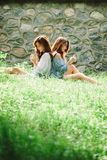 Two Asian Teen Females Relaxing Together in Heavenly Green Meadow, Idyllic Nature Scene royalty free stock image