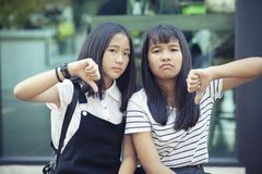 Two asian teenager hand sign thumb no good with not satisfy face stock photo