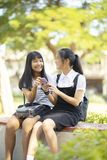 Two asian teenager happiness face holding smartphone in hand tal stock image
