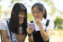 Two asian teenager laughing with happiness face reading message. In smart phone screen royalty free stock photography