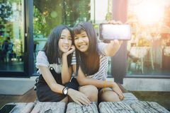Two asian teenager show white screen of smart phone screen and toothy smiling face happiness emotion stock images