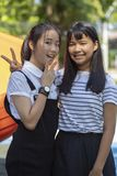 Two asian teenager smiling face and raising victory hand stock images