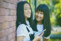 Two asian teenager toothy smiling face with happiness emotion ho. Ldhing smartphone in hand stock photography