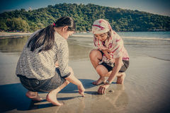 Two Asian Thai girls are digging to find shell on the beach Royalty Free Stock Image