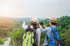 Two Asian tourists are taking pictures of the forest on the mountain. Travel in the holiday concept. Women backpack traveler girl adventure nature backpacker royalty free stock image
