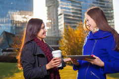 Two asian woman holding coffee and tablet in hand Royalty Free Stock Image