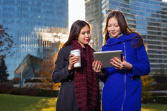 Two asian woman holding coffee and tablet in hand Royalty Free Stock Photography