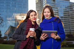 Two asian woman holding coffee and tablet in hand Stock Photography