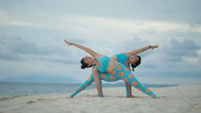 Two asian woman playing yoga pose on sea beach. Two asian woman  playing yoga pose on sea beach stock video