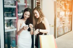 Two asian woman standing near window with happy watching smartph. Two asian women standing near window with happy watching smartphone at shopping mall center Royalty Free Stock Images