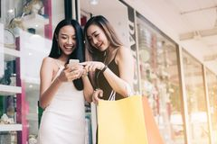 Two asian woman standing at store front with happy watching smart phone at shopping mall center. stock photography