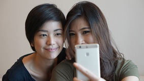 Two Asian woman taking photo, selfie using cell phone Royalty Free Stock Photos