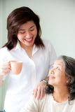 Two asian women. Smiling two asian women looking each other with a cup royalty free stock photos