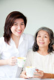 Two asian women. Smiling two asian women holding cups Stock Image