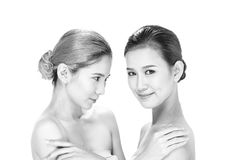 Two Asian women with beautiful fashion make up wrapped hair. Open shoulder clean skin, studio lighting white background isolated, black white concept Stock Image