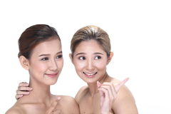 Two Asian women with beautiful fashion make up wrapped hair. Open shoulder clean skin, studio lighting white background isolated Royalty Free Stock Image