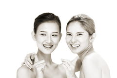Two Asian women with beautiful fashion make up wrapped hair. Open shoulder clean skin, studio lighting white background isolated Stock Photo