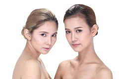 Two Asian women with beautiful fashion make up wrapped hair. Open shoulder clean skin, studio lighting white background isolated Stock Photography
