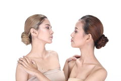 Two Asian women with beautiful fashion make up wrapped hair. Open shoulder clean skin, studio lighting white background isolated Royalty Free Stock Photography