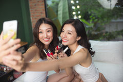 Two asian women in the bedroom on the bed  paint their nails and Stock Photos