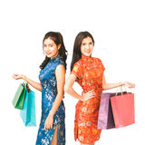 Two Asian women in Chinese qipao traditional dress holding shopping bags, Chinese new year or shopaholic girls concept Royalty Free Stock Photography