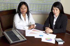 Two Asian Women at desk with laptop Royalty Free Stock Image