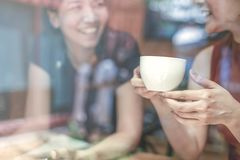 Two Asian women,friends having a free time drinking coffee at cafe. Friends laughing together while drinking a coffee in the. Coffee shop royalty free stock photography