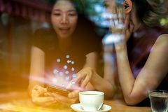 Two Asian women,friends having a free time drinking coffee at cafe. Friends laughing together while drinking a coffee in the. Restaurant, photo from outside the stock photography