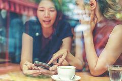 Two Asian women,friends having a free time drinking coffee at cafe. Friends laughing together while drinking a coffee in the. Restaurant, photo from outside the royalty free stock photos