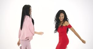 Two asian women having fun dancing like crazy at white background. People with party, celebration, enjoyment and new. Year concept. Slow Motion