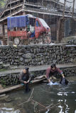 Two asian women rinse the laundry in river village, China. Stock Photos