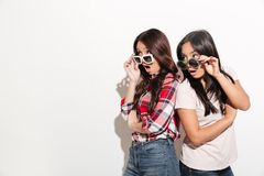 Two asian women sisters wearing sunglasses. Image of two asian women sisters wearing sunglasses standing isolated over white background. Looking aside Royalty Free Stock Images
