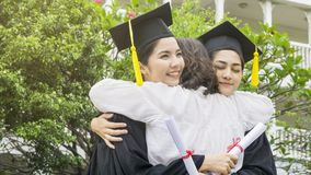 Two asian women smiles and feel happy in  graduation gowns and c. Ap and stand with the parent in the arm hug Royalty Free Stock Photos