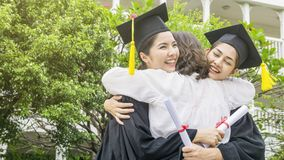Two asian women smiles and feel happy in  graduation gowns and c. Ap and stand with the parent in the arm hug Stock Image