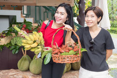 Two Asian women with tropical fruit Royalty Free Stock Images