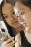 Two Asian women using cell phone. Two young Asian woman looking at the display of a cell phone Royalty Free Stock Photography