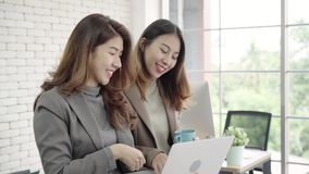 Two Asian young creative businesswomen holding a cup of coffee, working on laptop and disscuss about work while working in office. stock video