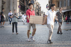 Two Asians carrying large cardboard box in the city downtown. Two Asians are carrying a large cardboard box helping. They are walking in the center of Piazza del royalty free stock photography