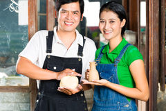 Asians with handmade pottery in clay studio. Two Asians or Indonesians holding proud baked clay and a finished handmade vase royalty free stock images