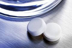 Two aspirin tablets. Close up shot of two aspirin tablets and drinking glass shot on stainless steel tray with overall cool blue tone Royalty Free Stock Photos