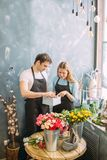 Two assistants picking up died flowers. Indoors Royalty Free Stock Photos