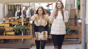 Two assured girls walking in furry coats outdoor. Slowly.  stock video