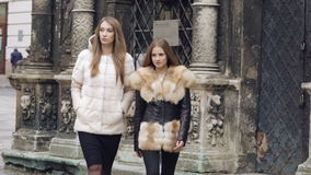 Two assured models walking runway in furry coats on the street. Slowly